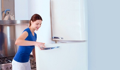 Lady opening energy efficient refrigerator