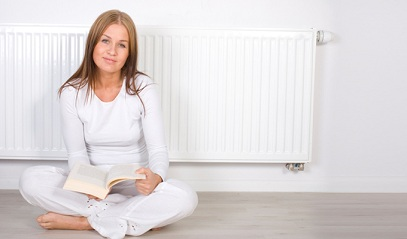 Women reading book in front of radiant heater