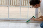 Man sealing screendoor