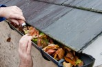 Man removing leaves from rain gutter