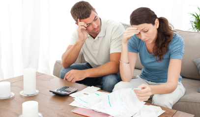 Couple reviewing utility bills at coffee table