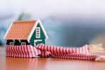 Miniature model home wrapped in scarf
