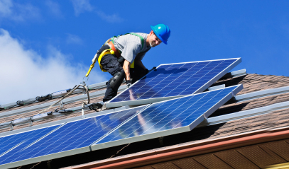 Contractor installing solar panels on a residential roof