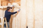 Man putting insulation on a wall in a home