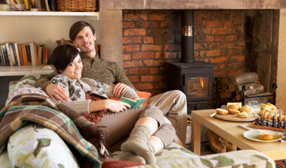 Couple on a sofa in front of a fireplace