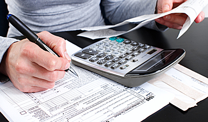 Woman calculating tax rebate using a calculator.