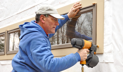 contractor using a nail gun to seal a window