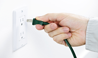 hand unplugging electrical plug from wall socket