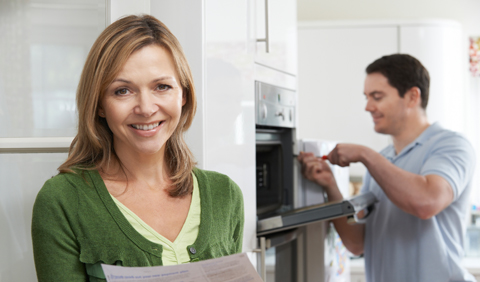 woman smiling as workman installs new stove