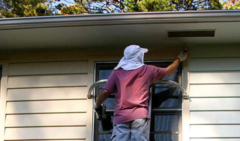 Man on ladder air sealing a window